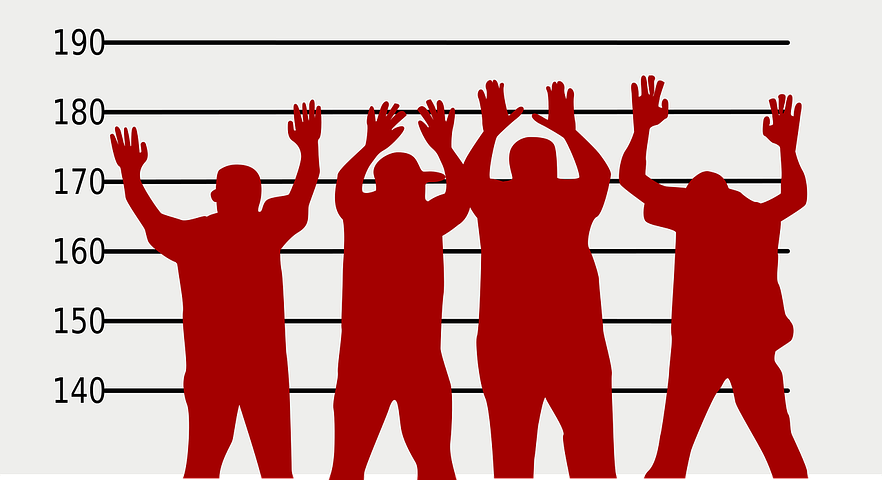crime suspects with their hands above their heads