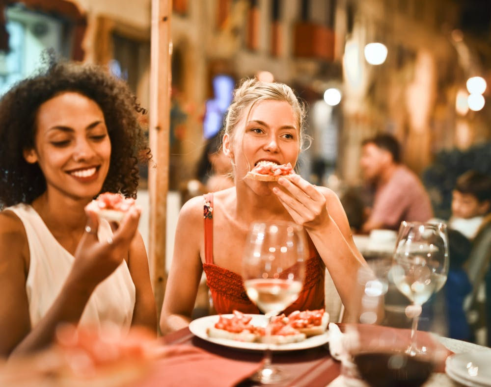 Two women eating pizza